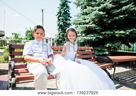 Brother And Sister At First Holy Communion Sitting On Bench Background Church.
