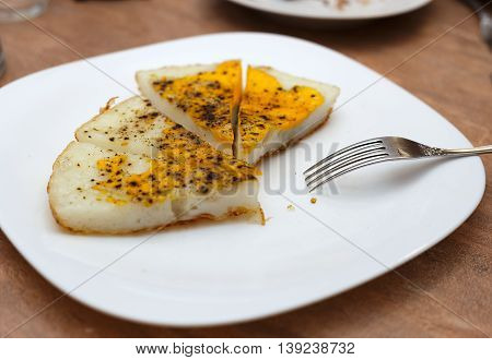 Huge fried ostrich egg cut into pieces on white plate horizontal side view