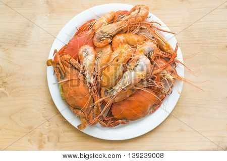 shrimp and Hot Steamed black Crabs in white dish