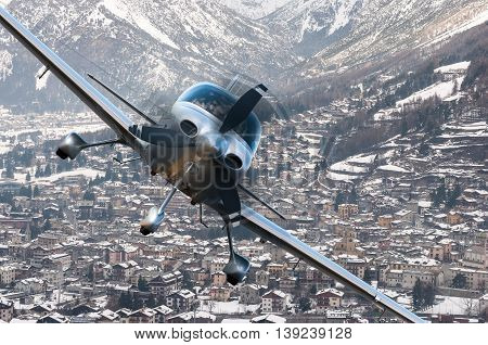 Privat plane or aircraft flight above winter resort city or village surrounded by mountains.