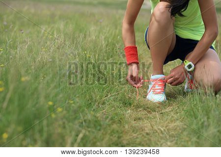 young fitness woman runner tying shoelace on nature trail