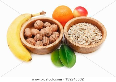 There are Banana,Apple,Orange with Walnuts in the Wooden Plate and Rolled Oats,with Green Leaves,Healthy Fresh Organic Food