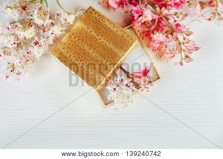 There Gold Open Box with White and Pink  Branches of Chestnut Tree are on White Table