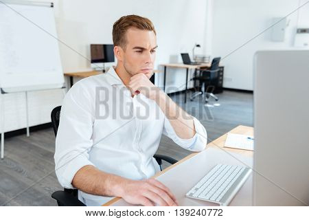 Thoughtful young businessman thinking and using computer at work