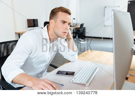 Thoughtful young businessman thinking and using computer in office