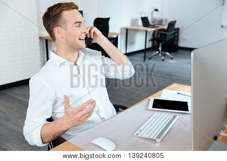 Happy handsome young businessman working and talking on mobile phone in office