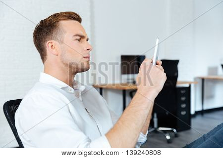 Serious conentrated young businessman sitting and using tablet at work