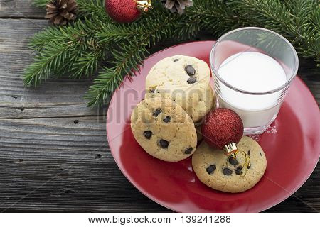 Homemade cookies with chocolate drops for the feast of Santa Claus in the new year surrounded by fir branches, Christmas toys and sweets. selective focus