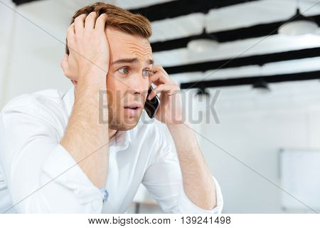 Stunned astonished young businessman talking on cell phone in office