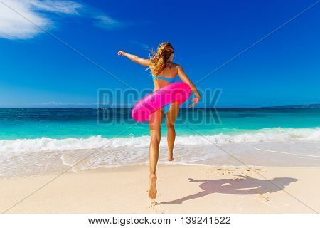 Young beautiful girl in blue bikini having fun on a tropical beach with rubber ring for swimming. Back to the viewer. Blue sea and sky in the background. Summer vacation concept.