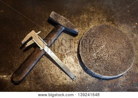 Old steel hammer with wooden handle iron heavy ring and calipers on the metal background