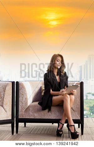 Beautiful happy businesswoman using digital tablet. Young woman using tablet computer in office . Woman working on his tablet office. Modern woman using tablet pc on sunrise background copy space.