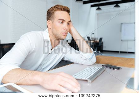 Sad bored young businessman sitting and working with computer in office
