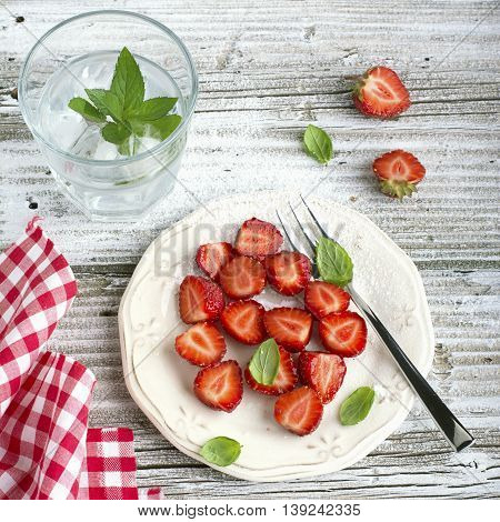 Healthy light breakfast snack. Strawberry slices with sugar, basil, mint for dessert on a light wooden background.