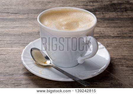 Cappuccino with milk foam on wooden background. A spoon with foam is placed on the saucer.