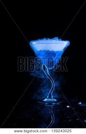 blue cocktail  and dry ice vapor over black background