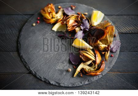 Baked artichokes with spices on wooden background
