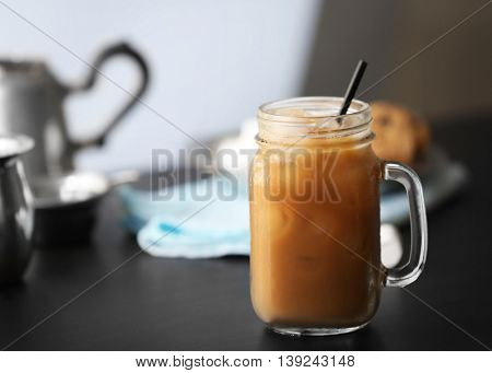 Iced coffee in glass jar on black table