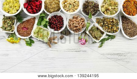 Natural flower and herb selection in ceramic bowls on wooden background