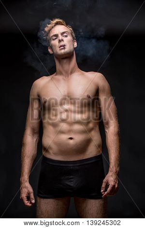 Macho with muscular body in black underpants stands on the black background in the studio. He smoke a cigarette and a smoke swirls around him. Vertical low-key photo.