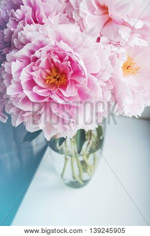 Beautiful bouquet of pink peonies, peony roses flowers in vase on white window sill, pastel color background. Spring or summer lovely nosegay. Fresh floral, home decor. Trend pink color. Text, copy space