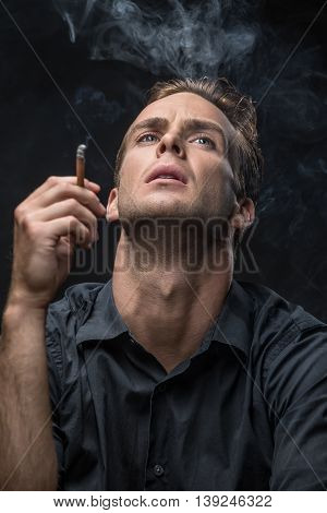Smoker in dark shirt looks up with parted lips on the black background in the studio. He holds a cigarette in the right hand. Smoke swirls around the man. Vertical low-key photo.