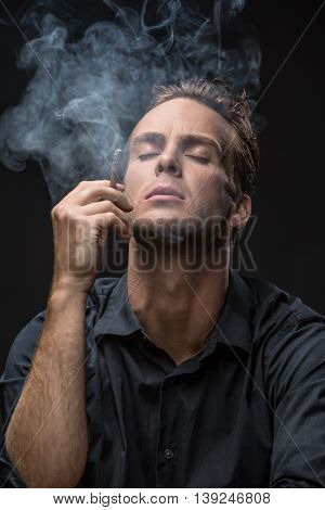 Elegant man in dark shirt smokes with closed eyes on the black background in the studio. He holds a cigarette in the right hand. Smoke swirls around him. Vertical low-key photo.