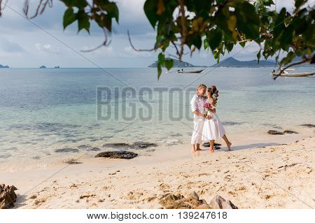 Elegant smiling young bride and groom walking on the beach, kissing and having fun, wedding ceremony near the rocks and ocean