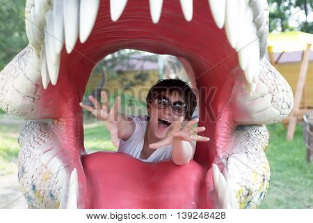 Portrait of woman in jaws of dinosaur