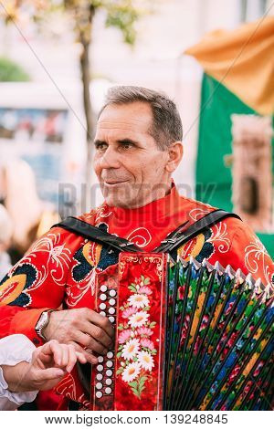 Gomel, Belarus - September 12, 2015: Unknown man in national clothes plays the accordion folk Belarusian music