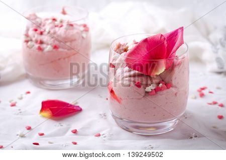 Strawberry dessert in glasses and pink rose, decorated with sugar hearts. Valentines Day background, selective focus