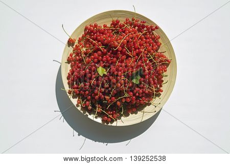 Top view on fresh harvest of red currant in wooden bowl lying on wooden table.