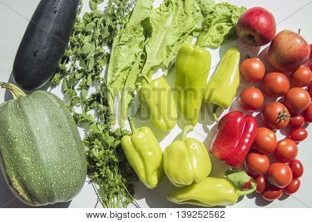 Fresh summer vegetables harvest from garden. Top view on multiple kinds of vegetables lying on white wooden table.