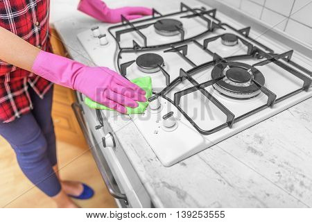 Hands in gloves are washed the gas stove. Close-up.