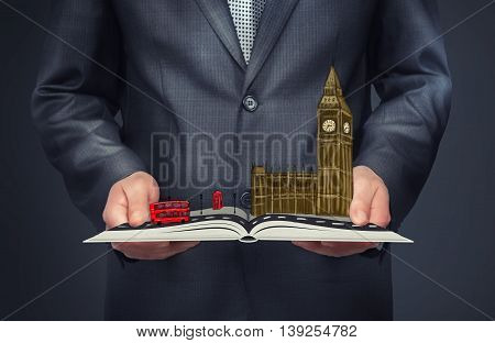 A businessman holding an open book with a sketch of London on the top of it. Big Ben, Palace of Westminster. Double-decker bus.. City of London. Leading global city in finance and business.