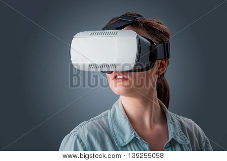 Excited young woman using a VR headset glasses and experiencing virtual reality on grey blue background