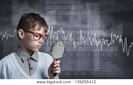 Cute boy looking through magnifying glass against graphs at chalkboard