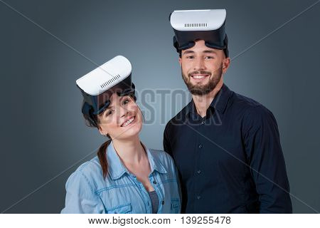 Excited young couple using a VR headset glasses and experiencing virtual reality on grey blue background. Looking at the camera