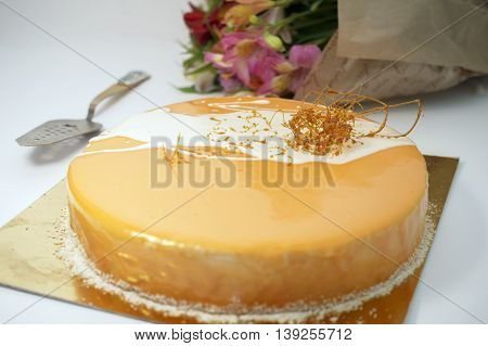 cake with orange frosting and caramel, flowers on background