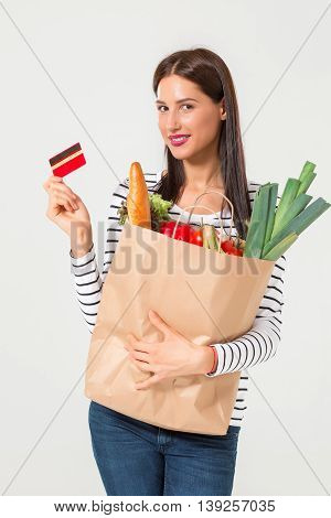 Beautiful young woman with credit card holding groceries in eco paper bag. Female consumer in shop. Concept of online shopping