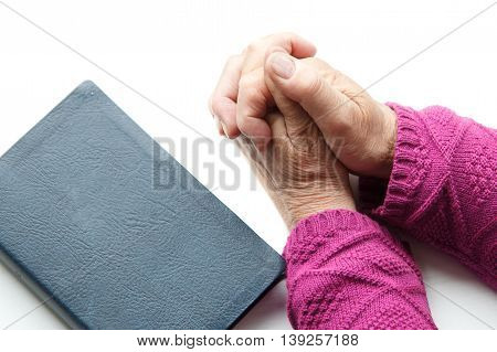elderly women hands crossed in prayer next to Bible
