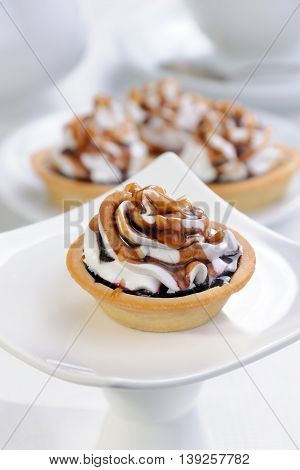 Shortbread сakes filled jam with whipped cream and chocolate caramel topping