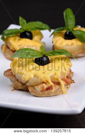 A piece of chicken with pineapple and cheese with olives and basil