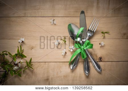 Spring table setting with cutlery and flowers. Silverware in spring scenery.