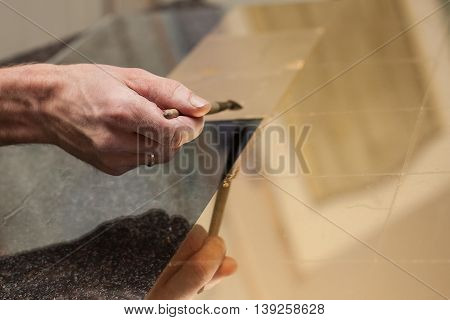 Master works with a thin gold leaf pieces on glass hands in the center of the frame