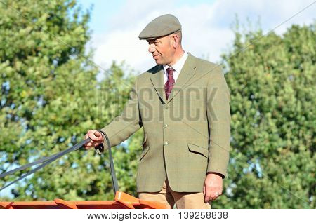 IPSWICH SUFFOLK UK 25 October 2014: East Anglia Equestrian Fair English country gent holding reins of Carthorse