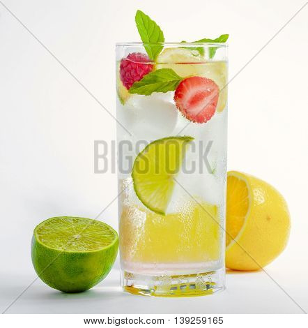 Refreshing cocktail with green mint, lime, lemon and berries on white background