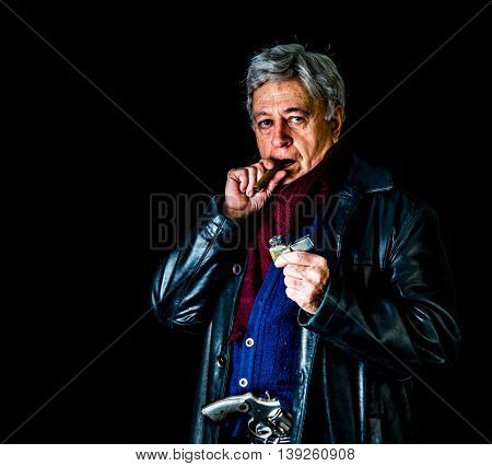 Low key shot of older man wearing a leather jacket sweater vest and scarf standing in front of a black backdrop and holding a cigar and lighter with a gun tucked into his waistband; the cigar is in his mouth.