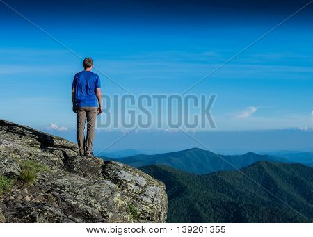 Male Hiker Stands Over Ridge Line looking onto green valley