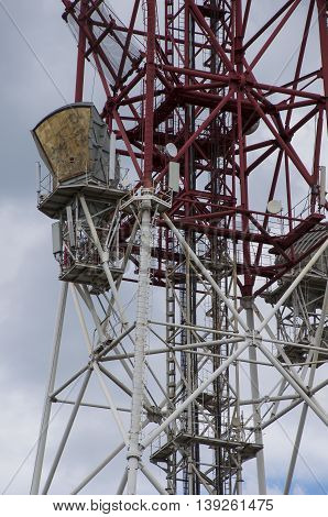Detail of a telecommunications tower among the gray clouds